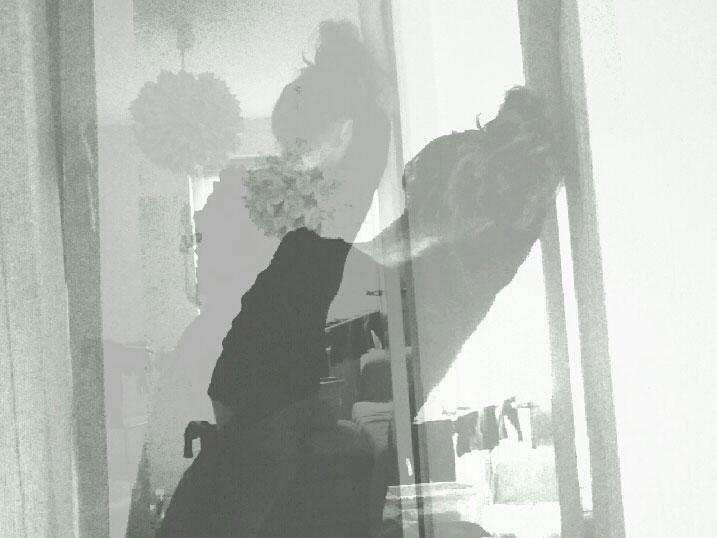 schwarz-weiß Fotografie einer Frau von hinten, die sich in Schieflage an einen Türrahmen lehnt