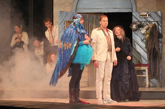 Als Vogel verkleideter Schauspieler mit Mann im weißene Anzug und Frau in schwarzem langen Kleid, Nebel im Hintergrund