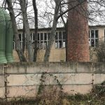 Fernwärmerohr, alter Schornstein und Werkshallenruine vor Betonplattenmauer in Magdeburg Nordwest 2019