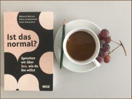 """Man sieht das Buch """"Ist das normal"""" mit einem Kaffee"""