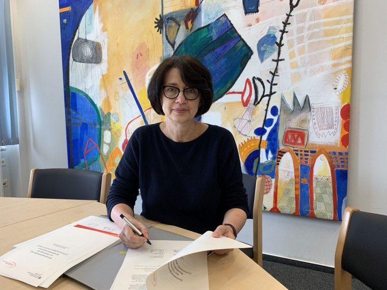Senatorin Claudia Bernhard unterzeichnet am Schreibtisch Verwaltungsvereinbarung