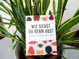 Buch mit dem Titel wie siehst du denn aus? steht dekorativ in einem Pflanzentopf
