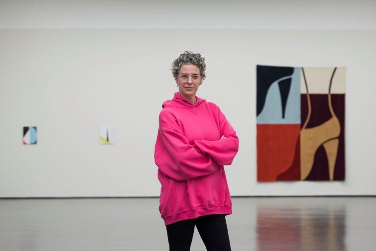 Ulrike Müller steht in einem pinken Pullover vor ihren Kunstwerken die an einer Wand hängen