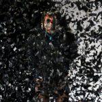 """Patrick Balaraj Yogarajan als Wahab in """"Im Herzen tickt eine Bombe"""" von Wajdi Mouawad auf der Bühne am Theater Bremen steht hinter aufgewirbelten schwarzen Papierschnipseln"""