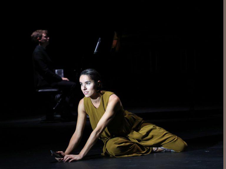 Monooper von Francis Poulenc am Theater Bremen: Sopranistin Nadine Lehner (vorne) sitzt auf dem Boden mit Telefon in der Hand & der musikalische Leiter Killian Farrell ist im Hintergrund am Klavier