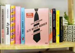 """Mehrere Bücher stehen in einem Bücherregal. Das Buch """"Alte weiße Männer"""" steht mit dem Cover sichtbar im Vordergrund."""