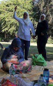 Zwei Frauen stehen bei sonnigem Wetter im Park und lachen die Kamera an. Eine Frau sitzt schmunzelnd auf einer Picknickdecke mit Chips und Getränken vor ihr