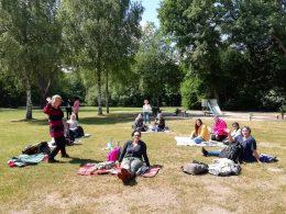 An einem sonnigen Tag sitzen Frauen verschiedenen Alters auf Picknickdecken im Park und winken der Kamera zu