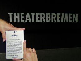 """Flyer des Tanztheaterstücks """"Futuralgia"""" vor schwarzer Wand mit Schriftzug """"Theaterbremen"""""""