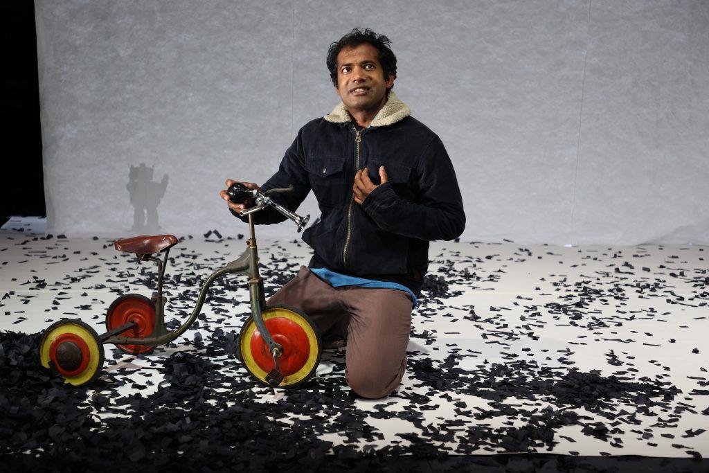 """Patrick Balaraj Yogarajan als Wahab in """"Im Herzen tickt eine Bombe"""" von Wajdi Mouawad auf der Bühne am Theater Bremen kniet vor einem Dreirad"""