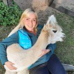 Frau kuschelt mit Alpaka