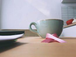 Kaffetasse mit rosa Schleife im Vordergrund