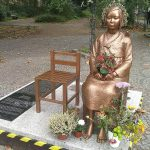 Die Bronzestatue eines Mädchens sitzt auf einem Holzstuhl auf einer Plattform aus weißem Marmor. Sie trägt traditionell koreanische Kleidung und hat echte Blumen im Schoß und zu ihren Füßen drapiert