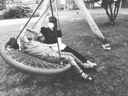 Schwarz-weiß Fotografie zweier Menschen auf einer Rundschaukel, Covid 19