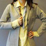Eine Frau ist vom Hals bis zur Hüfte zu sehen. Sie trägt einen Blazer mit gelbem Hemd
