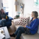4:3 Zwei Frauen sitzen auf zwei Sofas in einem Raum zusammen und reden. Die Frau auf dem beigen Sofa spricht und die Frau auf dem blauen Sofa hört lächelnd zu