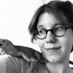 Lui Kohlmann, mit kurzen, dunklen Haaren schaut nach rechts zu einer Eidechse auf ihrer Schulter. Sie trägt eine runde Brille und ist in schwarz-weiß abgebildet
