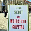 """Das Buch """"Das weibliche Kapital"""" wird hochgehalten. Im Hintergrund ist der Bremer Marktplatz. Eine Frau geht von der Kamera weg, weitere Menschen sind im Hintergrund zu erkennen"""
