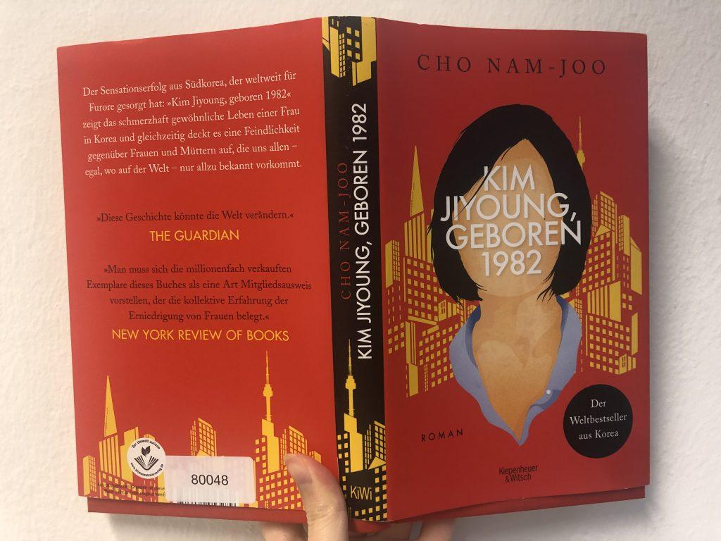 """Das Buch""""Kim Jiyoung, geboren 1982"""" wird vor weißer Wand gehalten"""
