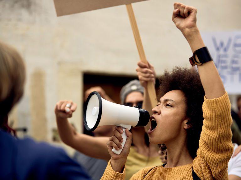 Portrait einer Frau, die auf einer Demonstration in ein Megaphon ruft