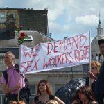 Protest von Sexarbeiter*innen, Zwei Männer heben die Fahne