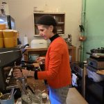 Frau hinter der Theke an einer Siebträgerkaffeemaschine