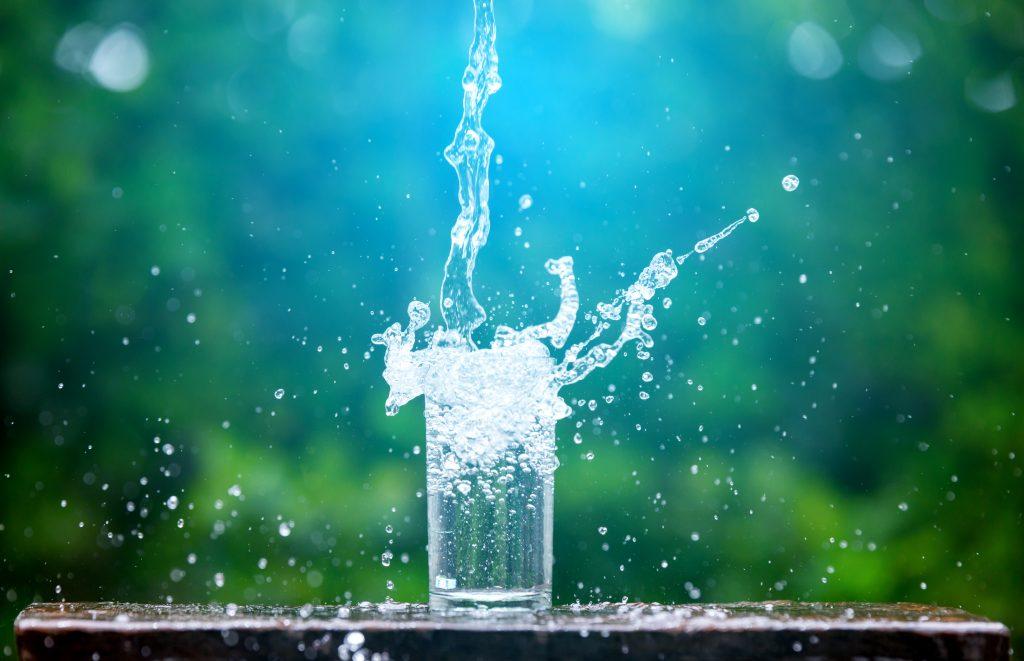 Stehendes Glas mit herausspritzendem Wasser