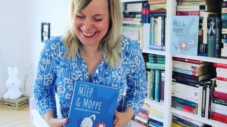Stine Oliver lachend mit Buch vor Bücherregal