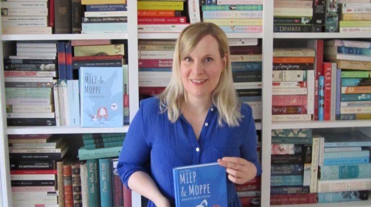 Stine Oliver mit Buch vor Bücherregal