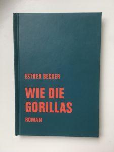 Ein gebundenes Buch. Die Farbe des Buchcovers ist in petrol gehalten. In auffälliger roter Schrift steht in Druckbuchstaben die Autroin, der Titel und das Genre geschrieben: Esther Becker. Wie die Gorillas. Roman