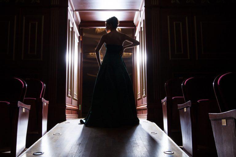 Rückansicht einer Frau im Kleid im Gegenlicht, in einer Theatertür stehend
