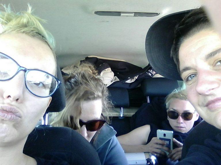 Foto von vier Personen im Auto. Zwei Personen sitzen vorne, schauen direkt in die Kamera. Zwei weitere Personen sitzen hinten und tragen eine Sonnenbrille. Eine schaut nach unten, die andere auf ihr Handy.