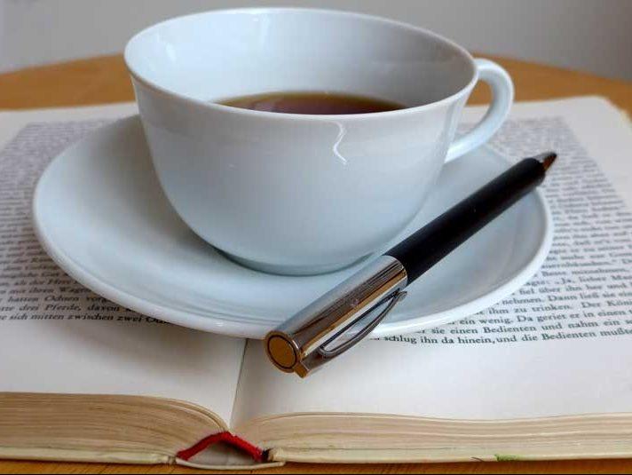 Tasse auf Buch mit Stift