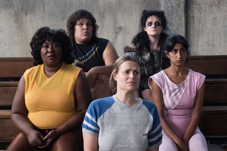 Fünf Frauen sitzen auf einer Treppe und schauen sehr gespannt.