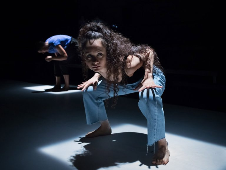 Frau in einer gebeugten, kampfbereiten Haltung in Mitten einer Theaterbühne, ausgestrahlt von Scheinwerfern.