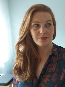 Portrait einer Frau mit langen Haaren die rechts an der Kamera vorbeischaut