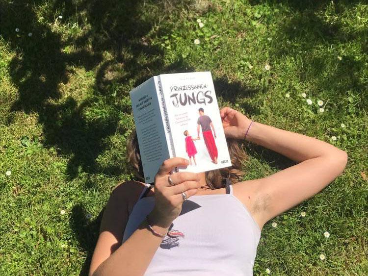 Frau liegt auf der Wiese und hält das Buch Prinzessinnen-Jungs vor ihr Gesicht