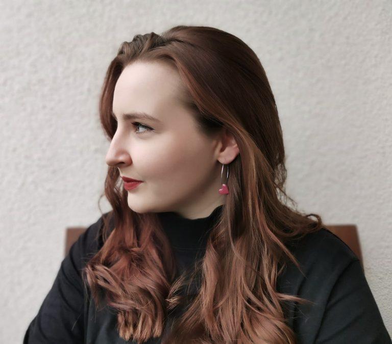 Foto einer Frau mit schwarzen Rollkragenpullover, die leicht lächelnd zur Seite schaut