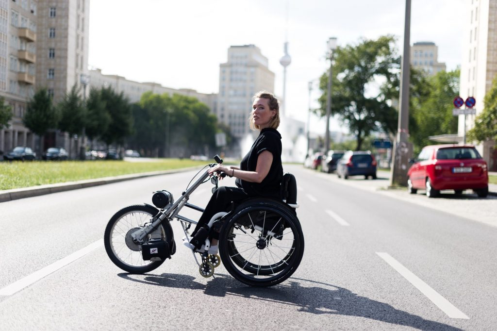 Junge Frau im dreirädrigen Rollstuhl, der wie ein Motorrad aussieht auf einer großen Straße in Berlin mit dem Fernsehturm im Hintergrund