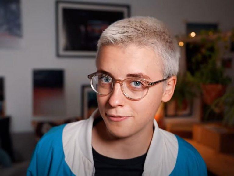 Man sieht einen Screenshot aus einem Youtube-Video von Annikazion. Die Frau mit hellblonden, sehr kurzen Haaren schaut forsch in die Kamera. Sie trägt eine helle Brille und eine blau-weiße Jacke.
