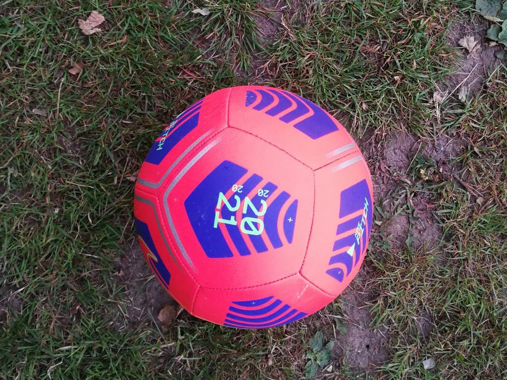 Ein neon-rosaner Fußball von oben auf einer Wiese fotografiert. Die Zahl 2021 steht auf dem Ball.