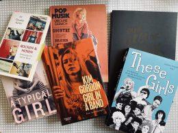 Sechs bunte Bücher liegen auf einer grau gemusterten Tischdecke.