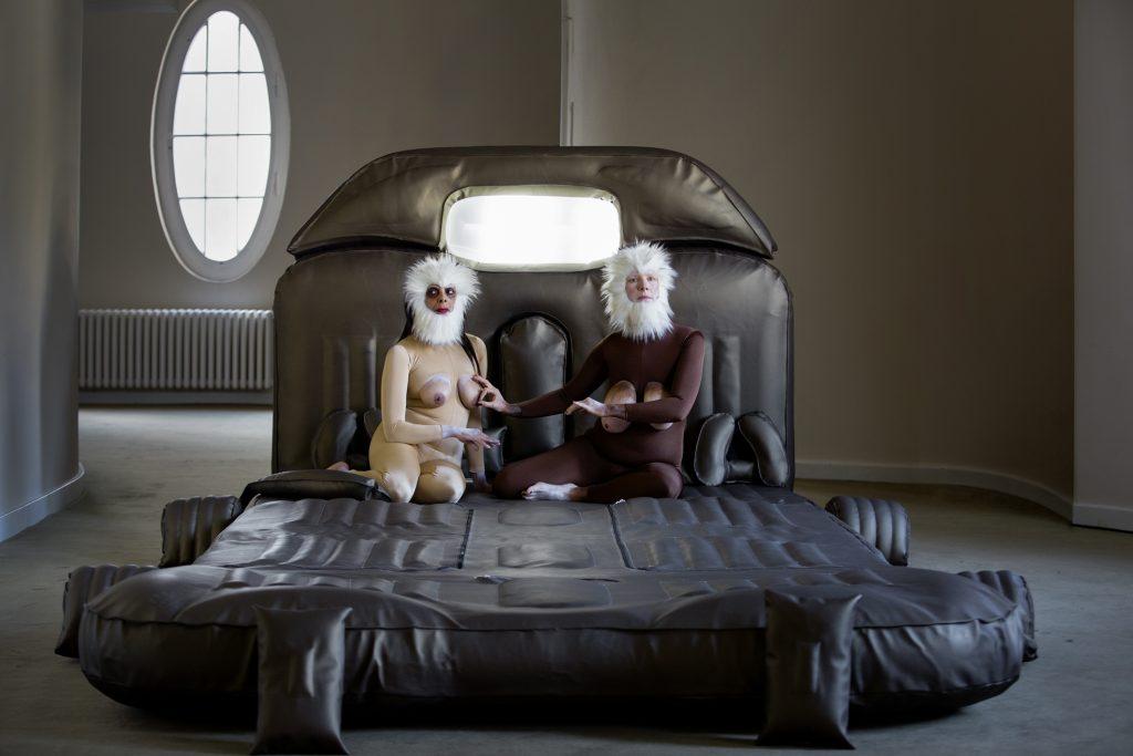 Ein Bild aus der Performance Consul und Meshie. Zwei als Affen verkleidete Menschen sitzen auf einem großen, schwarzen bettartigen Konstrukt. Beide schauen nach vorne, der rechte Affe fasst dem linken Affen an den Nippel.