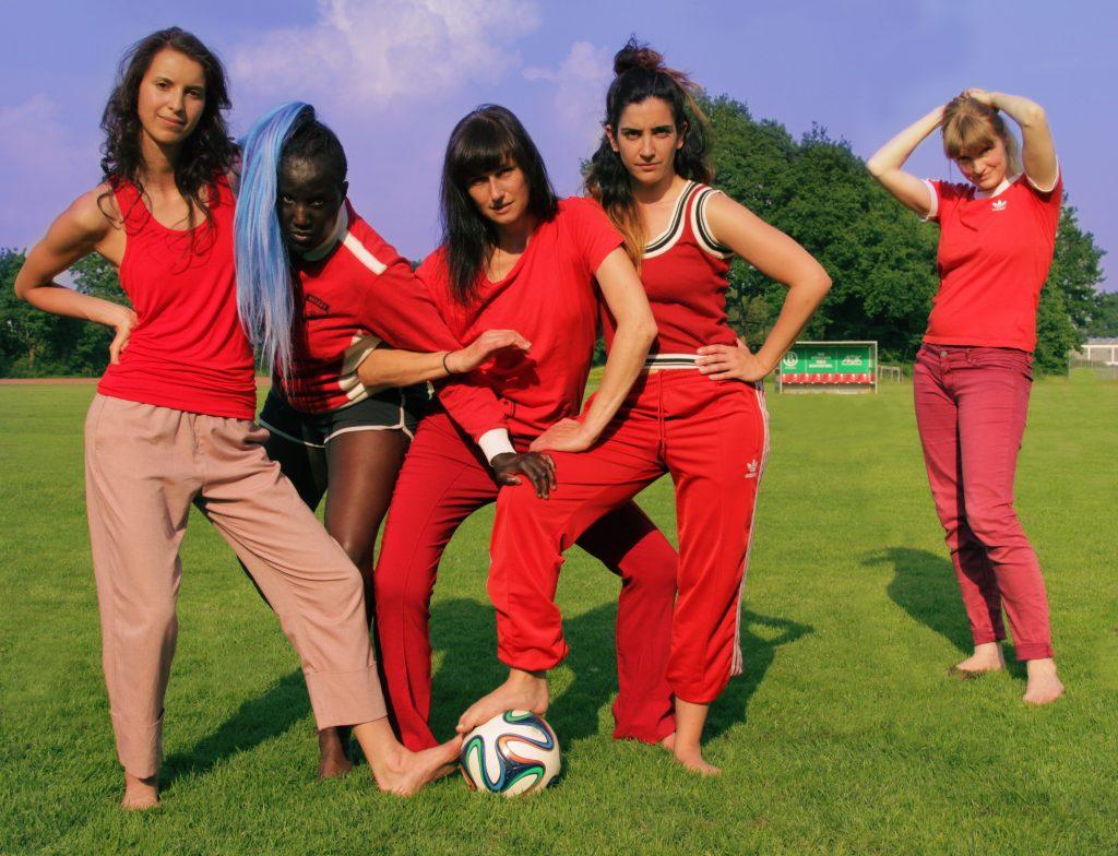 Man sieht fünf weiblich gelesene Personen, die in roten Sportklamotten gekleidet sind. Vier haben sich untergehakt und schauen herausfordernd in die Kamera, die fünfte Person steht etwas weiter hinten rechts und hält die Hände über ihrem Kopf.