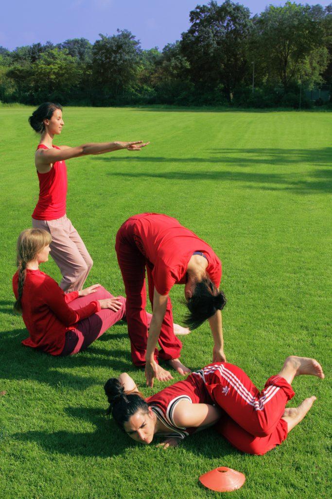 Vier weiblich gelesene Personen, die auf einem Fußballplatz performen, einige liegen auf dem Boden, einige machen Dehnübungen. Alle sind in roter Sportkleidunggekleidet.