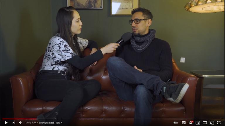 Moderatorin Joanna spricht mit dem Rapper B-Tight. Beide sitzen auf einem braunen Sofa.