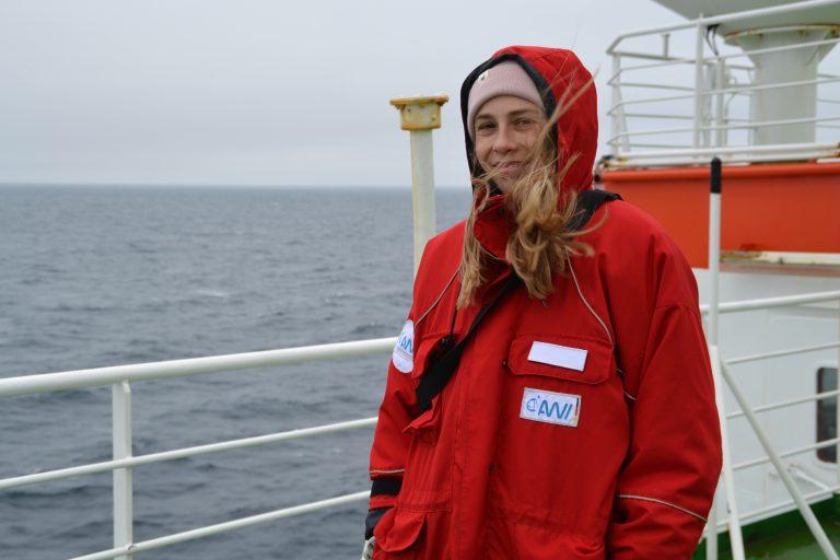 Frau in roter Regenjacke mit AWI-Logo, Mütze und blonden Haaren, die vom Wind verweht werden. Im Hintergrund erkennt man Teile eines Schiffes, grauen Himmel und das Meer. Die Frau lächelt.
