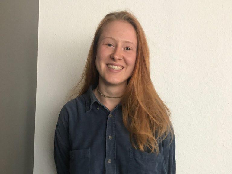 Portrait, junge Frau, weiße Wand, blaues Hemd, rote Haare