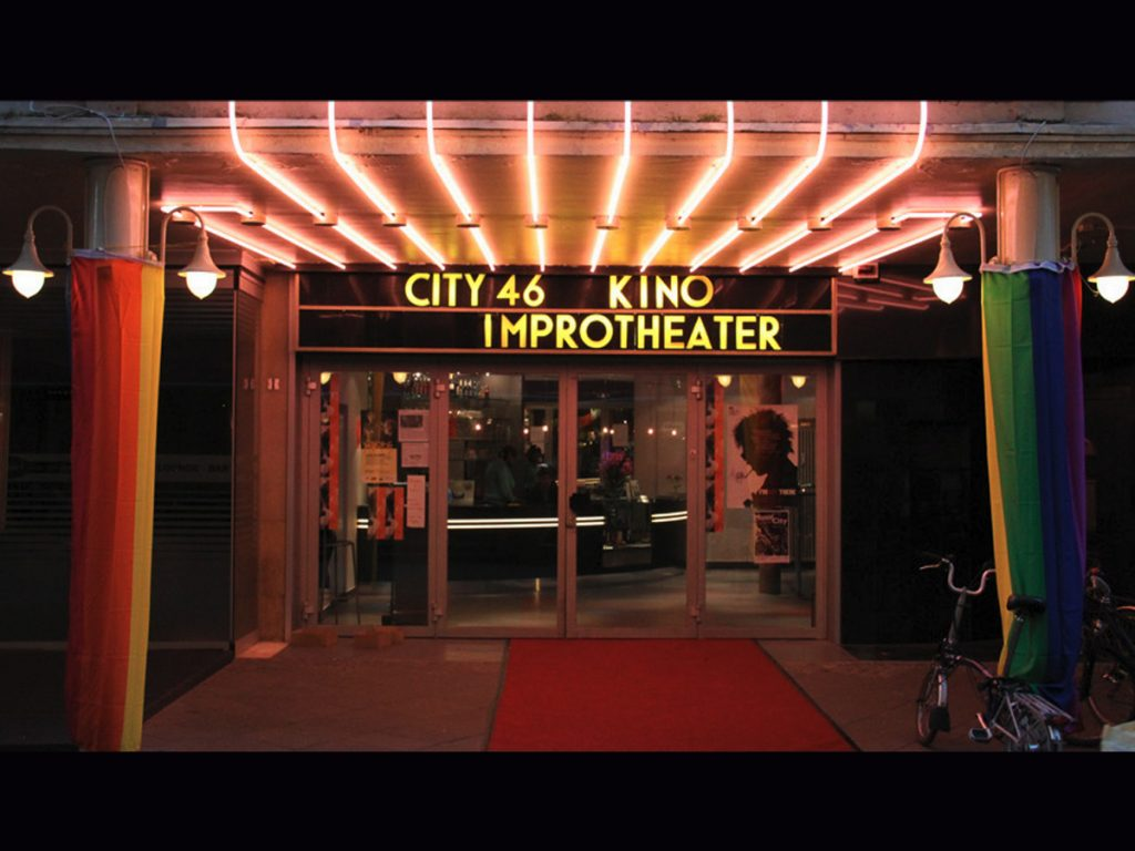 """""""City 46 Kino Improtheater"""" Eingang, Ganz viele Lampen, rechts und links Säulen mit Pride-flaggen, rechts Fahrräder an der Säule"""
