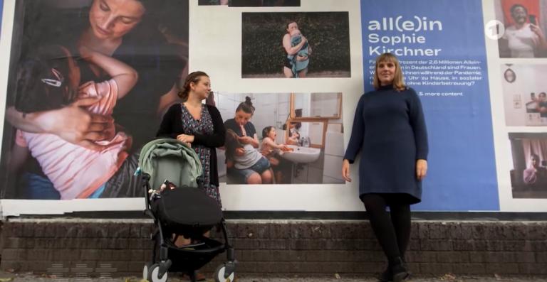 Zwei Künstlerinnen stehen vor einer Plakatwand, wo ihre Fotografien über alleinerziehende Mütter abgebildet sind.